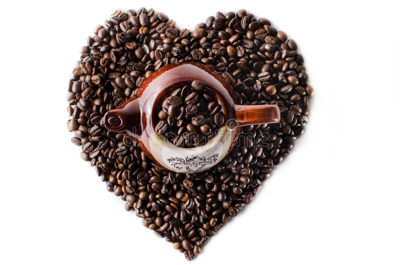 Coffee beans in the shape of a big heart with mug. Top view Kettle Isolated in white background stock image