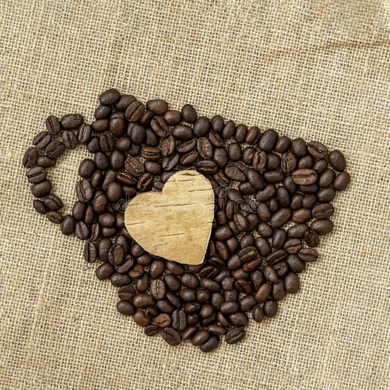 Coffee beans in the shape of a coffee cup with carved wooden heart on natural canvas, sackcloth. Concept of coffee love royalty free stock image