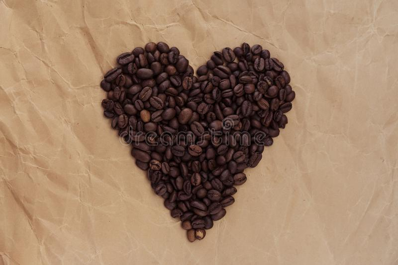 Coffee beans in the shape of heart on old paper royalty free stock photo