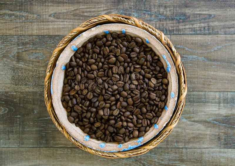 Coffee Beans sit in a Ceramic and Woven Straw Bowl stock image