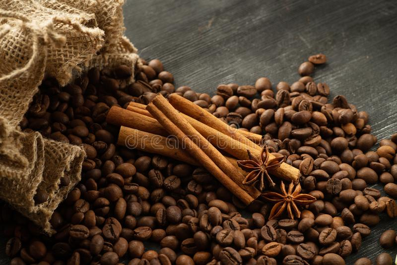 Coffee beans spill out of a bag with cinnamon sticks and star anise.  stock photos