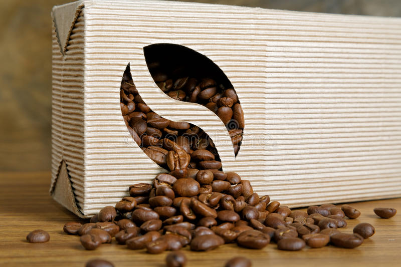 Coffee beans spill out of the box. On the table royalty free stock photography