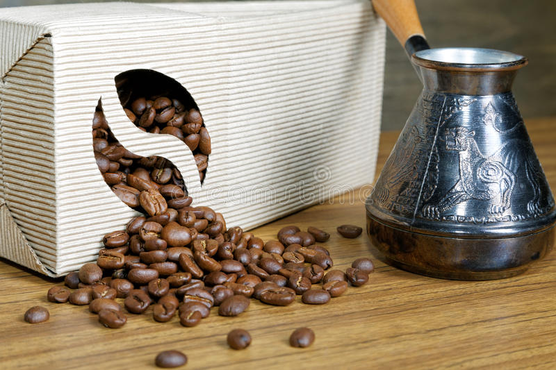 Coffee beans spill out of the box. On the table royalty free stock photo