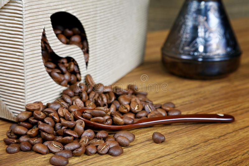 Coffee beans spill out of the box. On the table stock photography