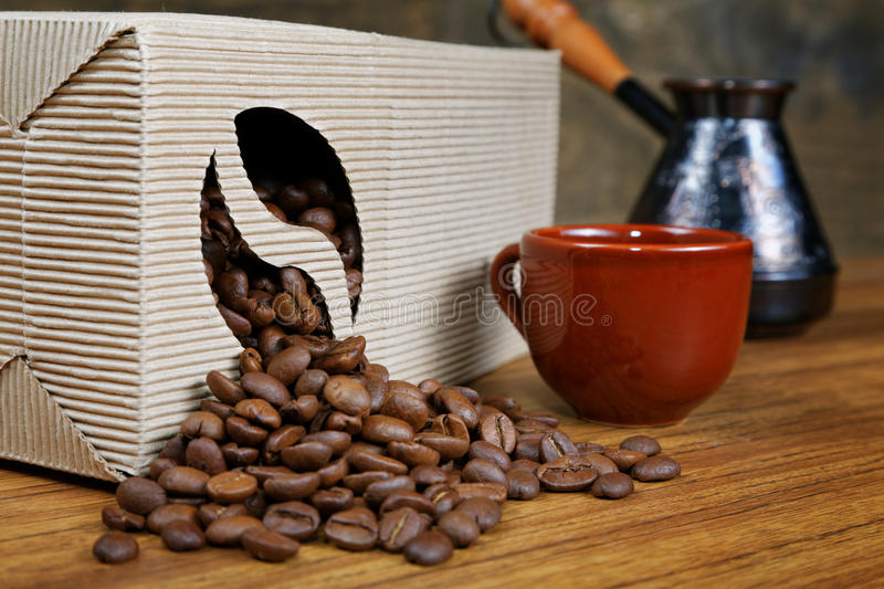 Coffee beans spill out of the box. On the table stock images