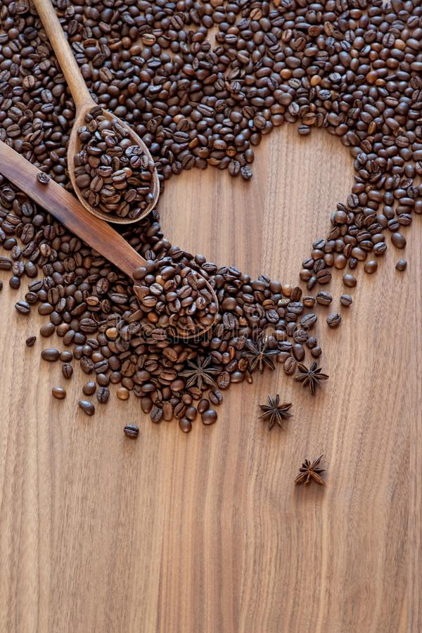 Coffee beans spilled on a heart-shaped wooden table with spices with two wooden spoons royalty free stock images