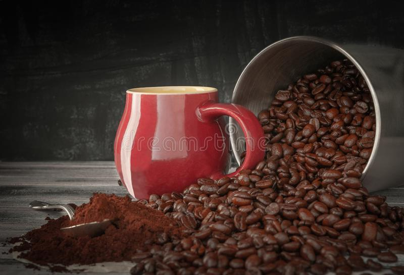 Coffee beans spilled out of a tin can onto a wooden table. Near the burgundy cup and freshly ground coffee. Photo in dark style royalty free stock image