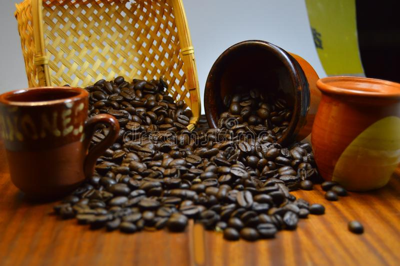 Coffee beans spilled on a wooden table. From old ceramic pots, photo from 2019 royalty free stock photo