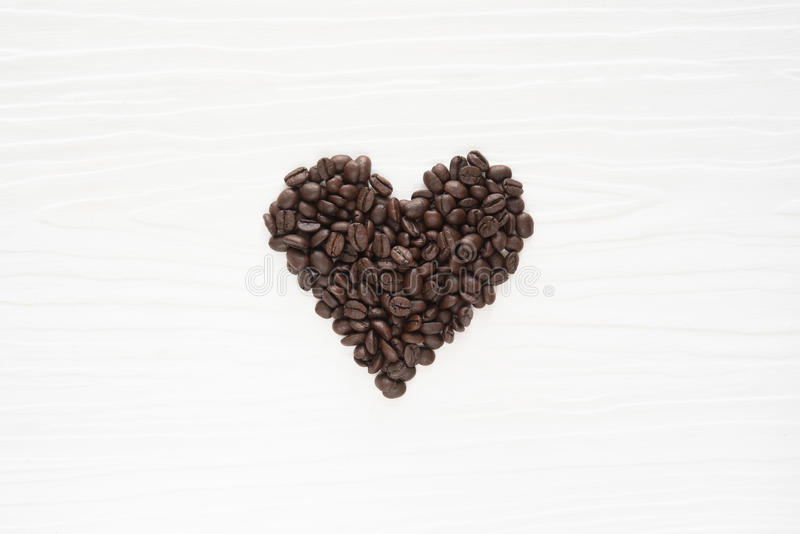 Coffee beans on a table in heart shape shot on white wooden stock images