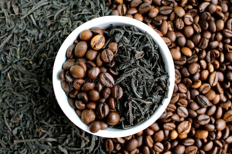 Coffee beans and tea in leaves on the same plate stock images