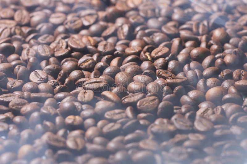 Coffee beans texture with smoke of prepared coffee. Black coffee beans texture with smoke of prepared coffee royalty free stock image