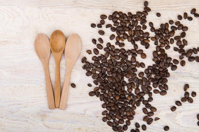 Coffee beans and three wooden spoons royalty free stock photo