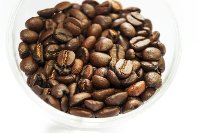 Coffee beans in a transparent cup on a white background stock photo