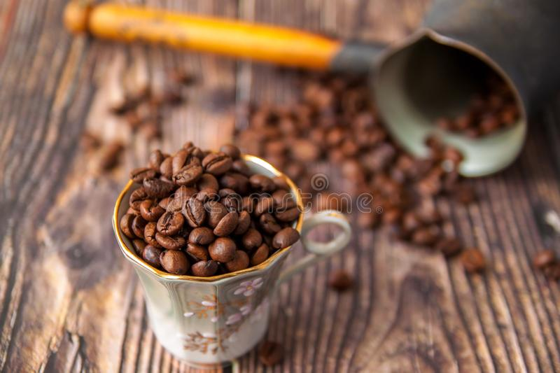 Coffee beans and turk on a wooden background. stock photo