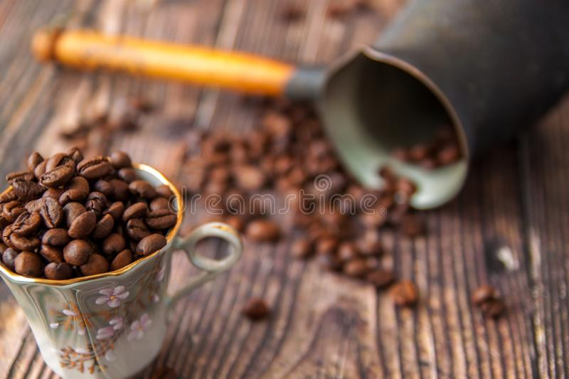 Coffee beans and turk on a wooden background. stock photos