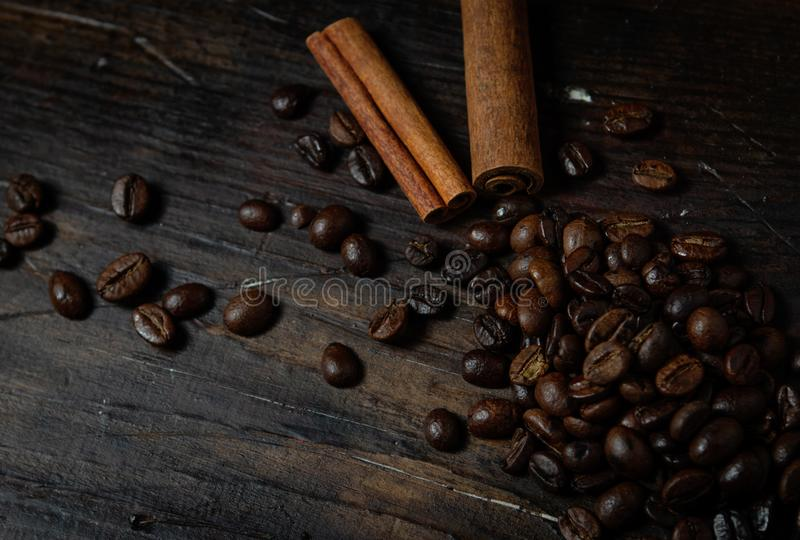 Coffee beans with two cinnamon sticks on a dark wooden background stock images