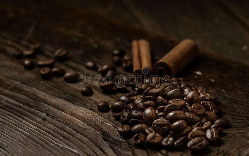 Coffee beans with two cinnamon sticks on a dark stock photos