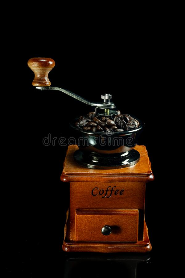 Coffee beans and vintage wooden coffee grinder on black background. Antique, aroma, bag, beverage, break, breakfast, brew, brewed, brown, cafe, caffeine royalty free stock photo