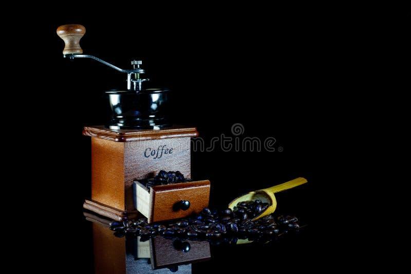 Coffee beans and vintage wooden coffee grinder on black background. Antique, aroma, bag, beverage, break, breakfast, brew, brewed, brown, cafe, caffeine stock image