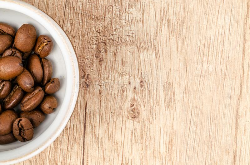 Coffee Beans on White Ceramic Bowl on Top of Brown Wooden Surface stock image