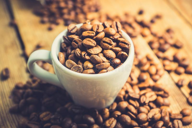 Coffee beans in white cup on the rustic wooden background. Selective focus. Shallow depth of field stock images