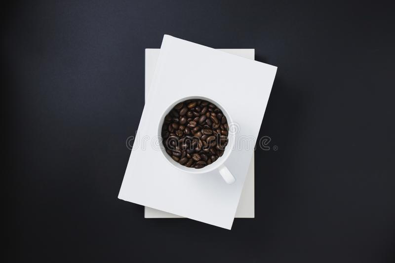 Coffee beans in a white coffee mug placed on white books stacked stock photos