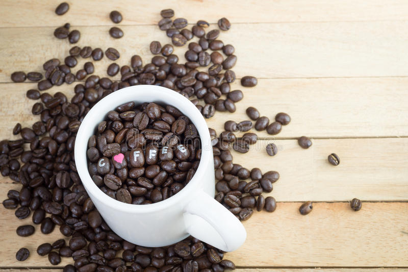 Coffee beans in white mug and wood background.  royalty free stock photography
