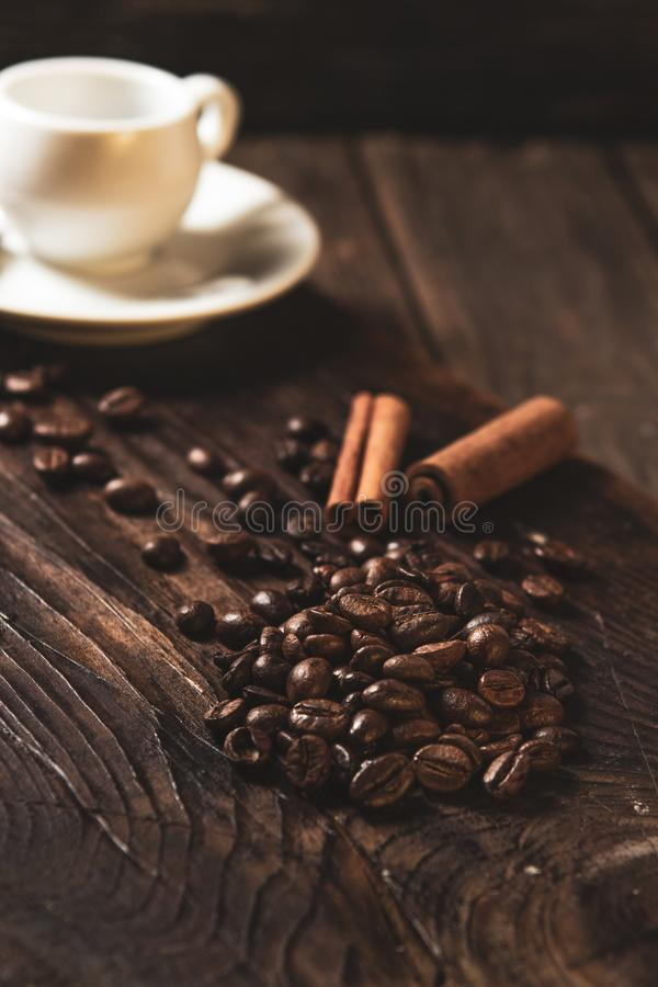 Coffee beans and white mug on wooden dark background royalty free stock photography