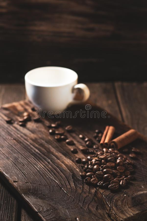 Coffee beans and white mug on wooden dark background stock photo