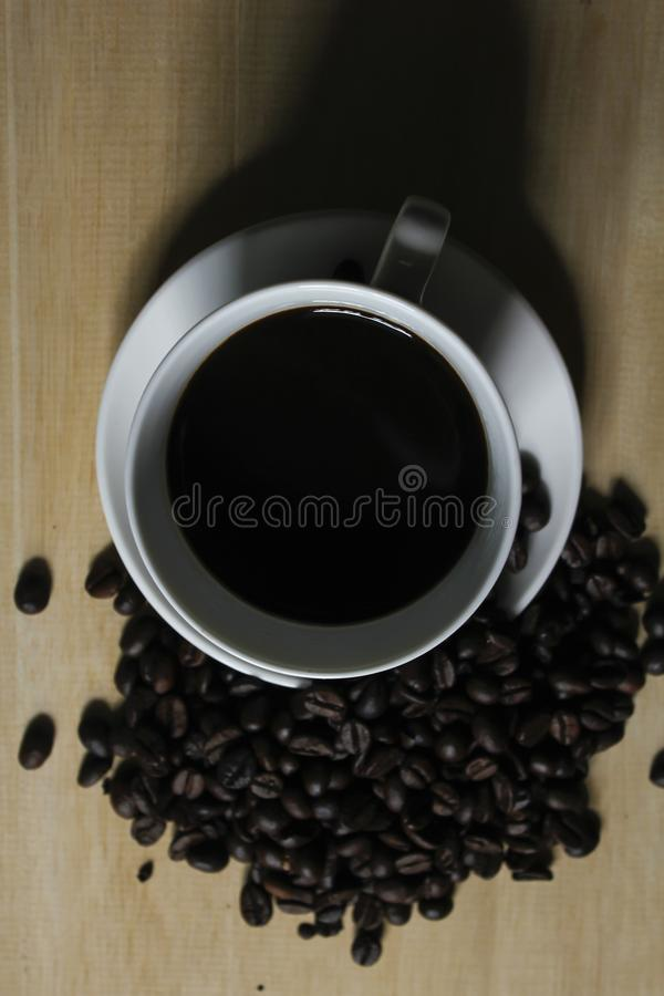 Coffee beans, white coffee mugs placed on wooden royalty free stock photos
