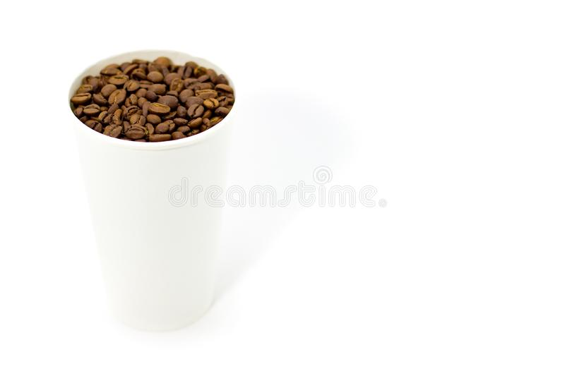 Coffee beans in a white paper cup on a white background. Place for text. Coffee beans in a white cup on a white background. Place for text royalty free stock images