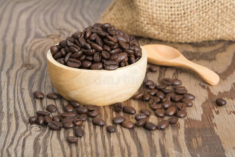 Coffee beans in wood spoon. And on old wood table royalty free stock photo