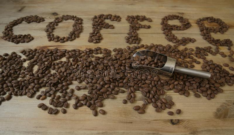 Coffee beans on a wooden background and the word `coffee` from coffee beans. Coffee beans on a wooden background and the word `coffee` from coffee brown beans royalty free stock photo