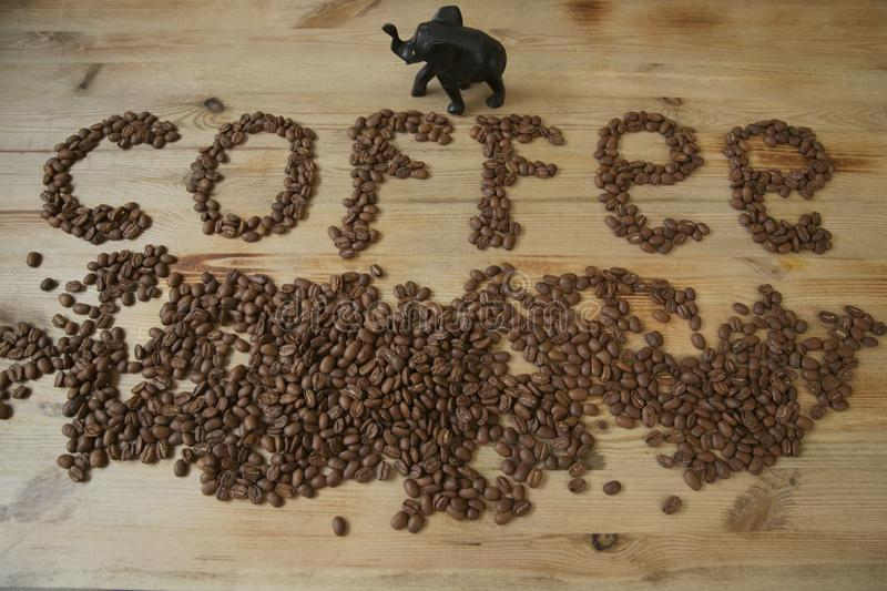 Coffee beans on a wooden background and the word `coffee` from coffee beans. Coffee beans on a wooden background and the word `coffee` from coffee brown beans stock images