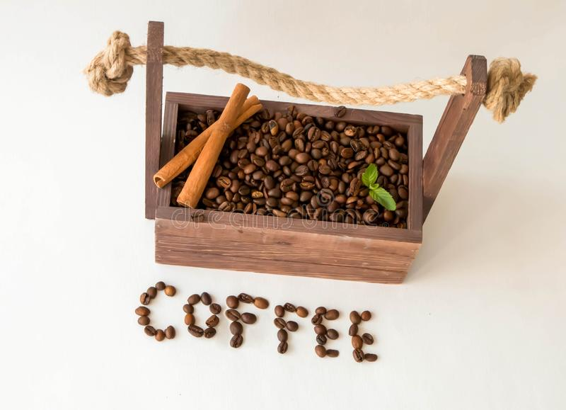 Coffee beans in a wooden box, on a white background with cinnamon stock photos
