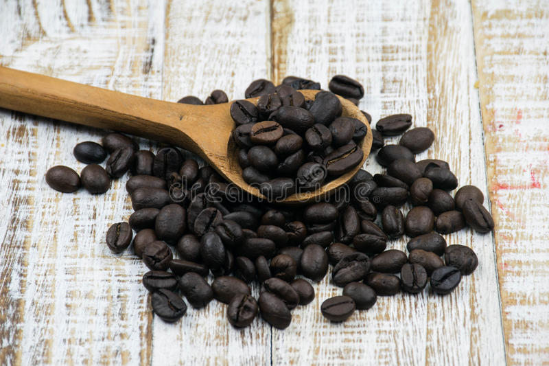 Coffee beans in a wooden spoon stock photo