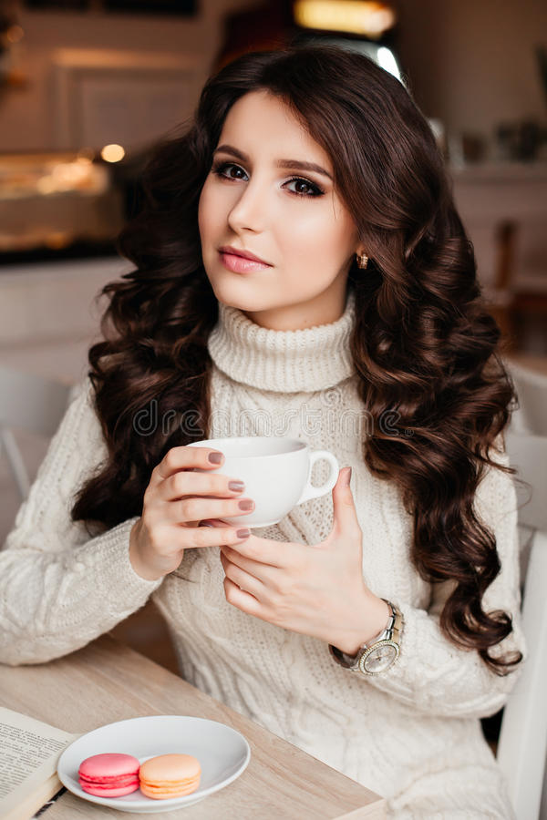 Coffee. Beautiful Girl Drinking Tea or Coffee. Cup of Hot Beverage. Brunette in a cafe drinking tea, eating sweets stock images