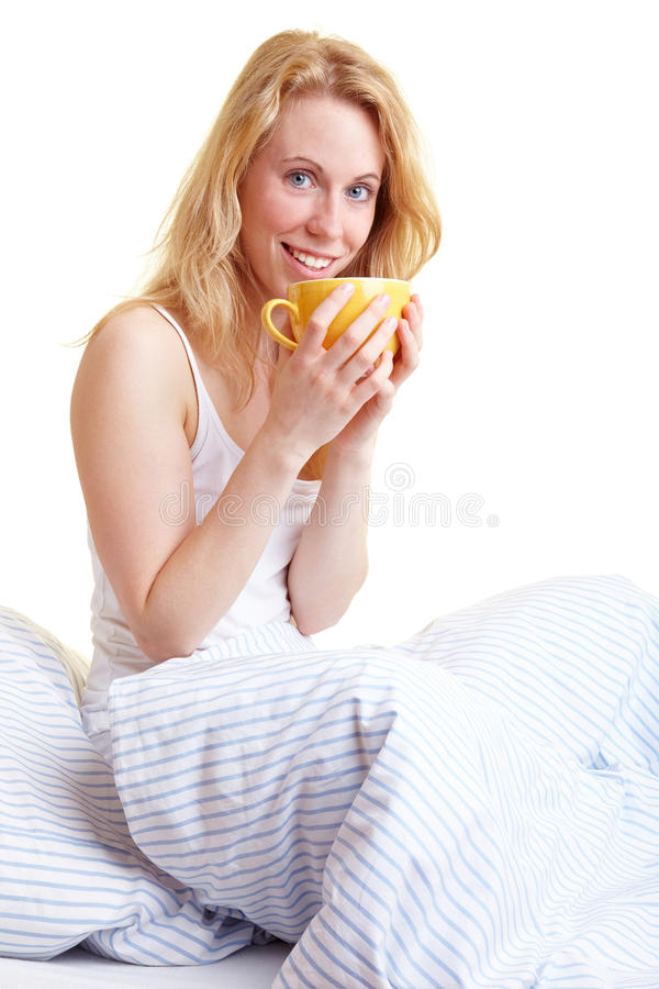 With coffee in bed. Happy blond woman drinking coffee in bed royalty free stock photography