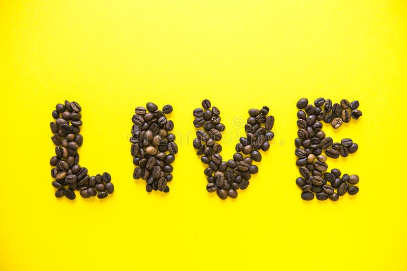 Coffee beens on yellow background. Word Food stock photos
