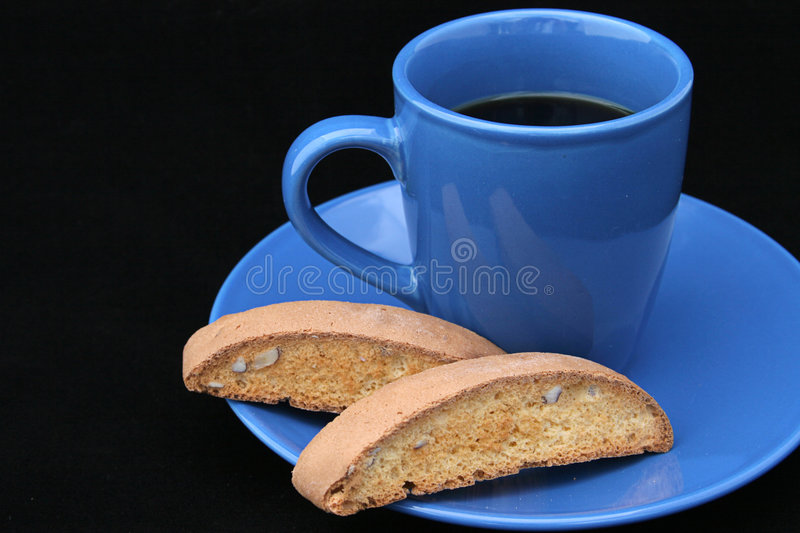 Coffee & Biscotti on Black. Black coffee in a bright blue cup, with biscotti on the side. Photographed on black background. (room for text stock photography