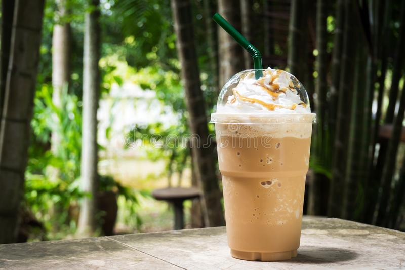 Coffee blend in plastic cup. Served with whipped cream topping and sweet syrup. royalty free stock photo