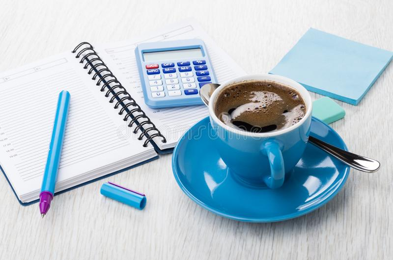 Coffee in blue cup, calculator, opened notepad, pen, eraser, pap stock photo