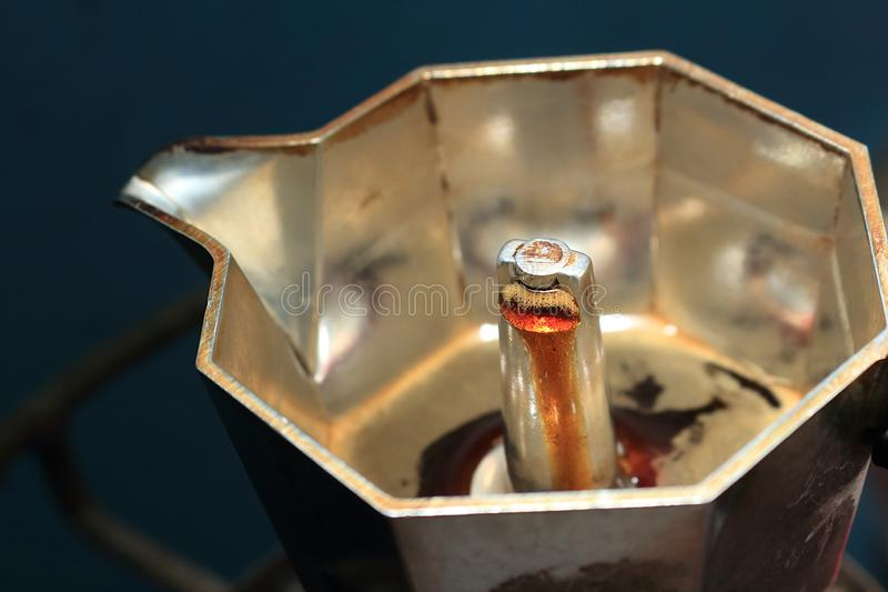 The coffee is boiling. Have crema flowing up on the moka pot royalty free stock photo