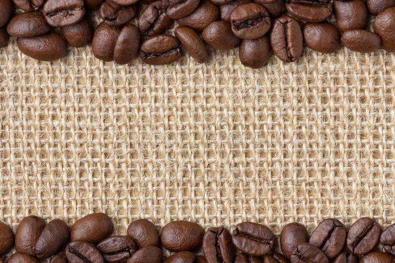 Coffee Border. Beans over burlap background royalty free stock photography