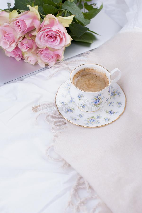 Coffee and bouquet of pink roses in bed, romance and coziness. Good morning. Breakfast in bed. Copy space.  stock photography