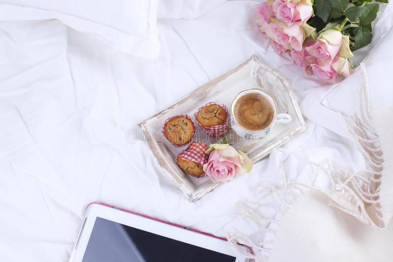 Coffee and bouquet of pink roses in bed, romance and coziness. Good morning. Breakfast in bed. Copy space.  royalty free stock images