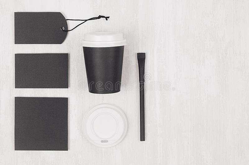 Coffee branding identity mockup in light modern style - black paper cup, blank card, label, sugar, white cap on white wood board. Coffee branding identity royalty free stock photos