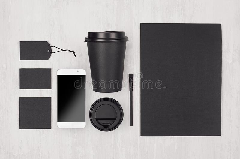 Coffee branding identity mockup in light modern style - black paper cup, blank screen phone, card, label, paper, cap on white wood stock images