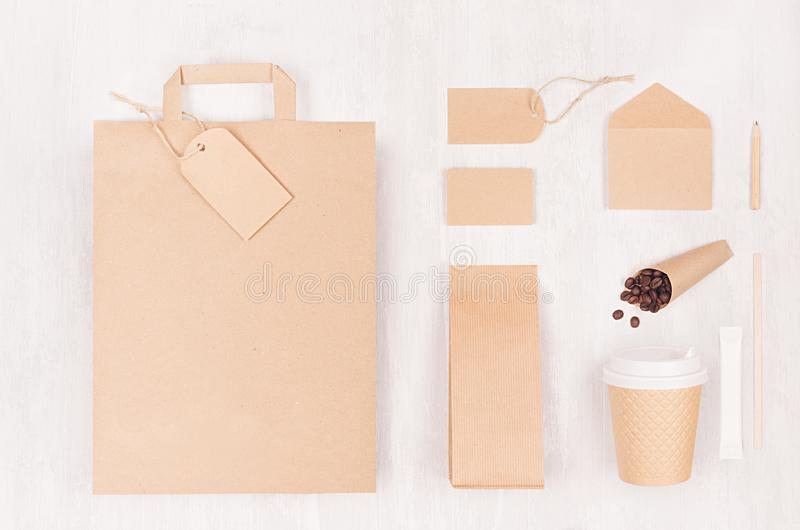 Coffee branding identity mockup - set of brown paper cup, blank bag, packet, label, card, stationery, coffee beans on white wood. stock photos