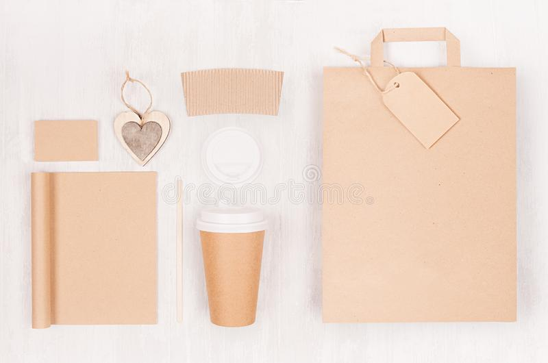 Coffee branding mockup - brown paper cup with blank bag, notebook, label, cap, card, heart on white wood board, top view. stock images